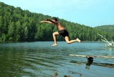 男孩跳的湖 免版税库存图片