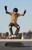 男孩跳的滑板 免版税库存图片