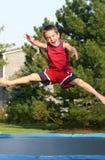 男孩跳的绷床 免版税库存照片