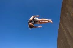 男孩跳跃的翻筋斗蓝色Parkour 库存图片