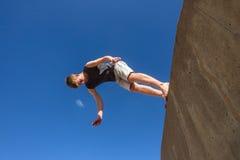 男孩跳跃的翻筋斗Parkour天空 免版税图库摄影