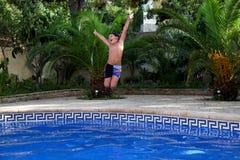 男孩跳进游泳池 免版税图库摄影