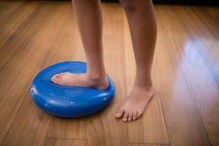 男孩身分的低部分,当跨步在大蓝色重音球时 免版税库存照片