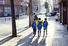 男孩运动员从训练去在巴塞罗那街道上的橄榄球  免版税库存照片