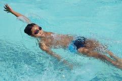 男孩运动员是训练的仰泳为准备以后的每年游泳体育比赛 免版税库存图片