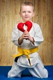 男孩运动员空手道给心脏,爱,同情的声明 在席子的空手道在健身房 免版税库存照片