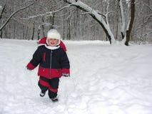 男孩运行冬天木头 免版税库存图片