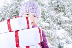 男孩运载在雪背景的圣诞节礼品 库存图片