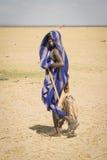 男孩运载从图尔卡纳湖,肯尼亚的干鱼 免版税库存照片