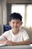 男孩选件类完成本级教室工作 库存图片