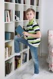 男孩选择书读 免版税库存图片