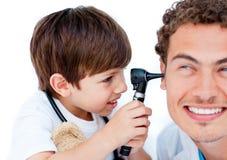 男孩逗人喜爱的医生使用他的一点 库存照片
