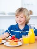 男孩逗人喜爱的吃草莓奶蛋烘饼 免版税库存照片