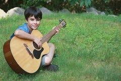 男孩逗人喜爱的吉他使用的一点 库存图片