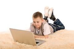 男孩逗人喜爱的膝上型计算机使用 免版税库存图片