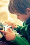 男孩逗人喜爱的膝上型计算机使用 图库摄影