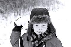 男孩逗人喜爱雪球投掷 免版税库存图片