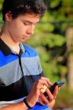 男孩逗人喜爱青少年texting 图库摄影