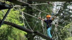 男孩通过吊桥走,他头戴奥尔讷斯和盔甲 股票视频