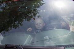 男孩通过挡风玻璃 库存照片