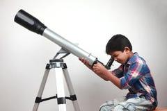 男孩通过望远镜看 免版税库存图片