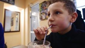 男孩通过秸杆,特写镜头喝奶昔 股票视频