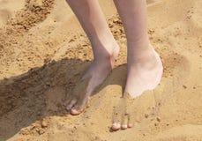 男孩部分埋没了英尺沙子 库存照片