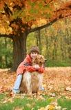 男孩金黄拥抱的猎犬 免版税库存图片