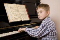 男孩钢琴使用 图库摄影
