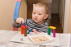 男孩铸造彩色塑泥 免版税库存图片