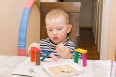 男孩铸造彩色塑泥 免版税库存照片