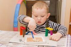 男孩铸造彩色塑泥 免版税图库摄影