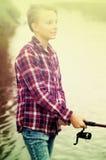 年轻男孩铸件线画象钓鱼的 库存照片