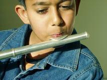 男孩长笛使用 免版税库存图片
