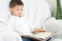 男孩阅读书和惊奇 图库摄影