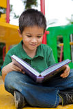 年轻男孩阅读书在操场 免版税库存图片