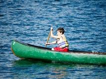 男孩阵营乘独木舟的夏天 图库摄影
