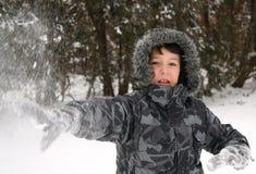男孩雪投掷 免版税图库摄影