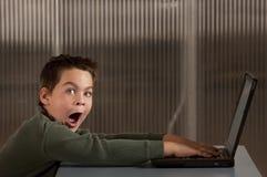 男孩震惊的计算机膝上型计算机 免版税库存图片
