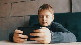 男孩青少年使用在一个时髦的咖啡馆的黑智能手机 影视素材