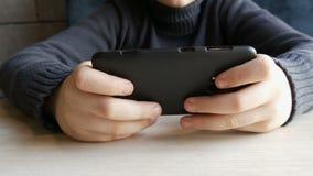 男孩青少年使用的手在一个时髦的咖啡馆的黑智能手机 在行动的照相机 股票录像