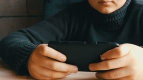 男孩青少年使用的手在一个时髦的咖啡馆的黑智能手机 股票视频