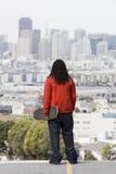 男孩青少年藏品的滑板 免版税库存照片
