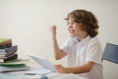 男孩非常疲倦做家庭作业 免版税库存图片