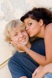 男孩面颊女孩亲吻的年轻人 免版税库存照片