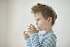 年轻男孩饮用奶的侧视图 库存图片