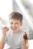 男孩饮用的咳嗽糖浆 免版税库存图片