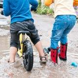 男孩骑自行车,并且女孩乘坐横跨深水坑的一辆滑行车 库存图片