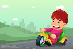 男孩骑马三轮车 库存图片