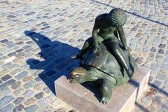 男孩骑马乌龟雕象  库存图片